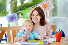 Χαριτωμένο μικρό παιδί που σύρει και που χρωματίζει με τις ζωηρόχρωμες μάνδρες δεικτών στον παιδικό σταθμό Στοκ Φωτογραφίες