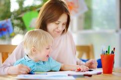 Χαριτωμένο μικρό παιδί που σύρει και που χρωματίζει με τις ζωηρόχρωμες μάνδρες δεικτών στον παιδικό σταθμό Στοκ φωτογραφία με δικαίωμα ελεύθερης χρήσης