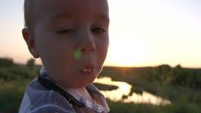Χαριτωμένο μικρό παιδί που τρώει την μπανάνα στον τομέα και ευτυχώς τα τρεξίματα στο ηλιοβασίλεμα, σε αργή κίνηση απόθεμα βίντεο
