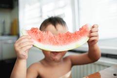 Χαριτωμένο μικρό παιδί που τρώει το καρπούζι στην κουζίνα στοκ φωτογραφία με δικαίωμα ελεύθερης χρήσης