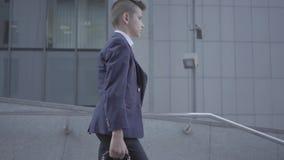 Χαριτωμένο μικρό παιδί που φορά ένα επιχειρησιακό κοστούμι με την περίπτωση που περπατά στην πόλη Παιδί όπως ενήλικο φιλμ μικρού μήκους