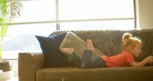 Χαριτωμένο μικρό παιδί που χρησιμοποιεί την ψηφιακή ταμπλέτα στο καθιστικό στο σπίτι 4k απόθεμα βίντεο