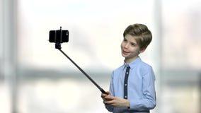 Χαριτωμένο μικρό παιδί που χρησιμοποιεί selfie το ραβδί απόθεμα βίντεο