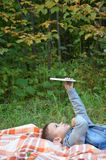 Χαριτωμένο μικρό παιδί σε ένα πάρκο φθινοπώρου σε ένα κάλυμμα Διαβάζει στα παιχνίδια μια ταμπλέτα ηλεκτρονικός ασύρματος ψηφιακός στοκ φωτογραφίες
