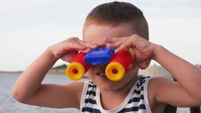 Χαριτωμένο μικρό παιδί με τις διόπτρες στην ακτή απόθεμα βίντεο