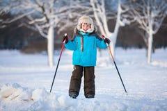 Χαριτωμένο μικρό παιδί που έχει τη διασκέδαση κατά τη διάρκεια να κάνει σκι στο σταυρό Στοκ Φωτογραφία