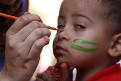 Χαριτωμένο μικρό παιδί που έχει χρωματισμένα τα πρόσωπο παιδιά του που έχουν το παιχνίδι διασκέδασης Στοκ Φωτογραφία