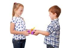 Χαριτωμένο μικρό παιδί που δίνει ένα παρόν στο κορίτσι στοκ εικόνες