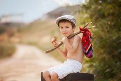 Χαριτωμένο μικρό παιδί, που κάθεται σε μια μεγάλη παλαιά βαλίτσα, τρύγος, κράτημα Στοκ εικόνες με δικαίωμα ελεύθερης χρήσης