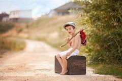 Χαριτωμένο μικρό παιδί, που κάθεται σε μια μεγάλη παλαιά βαλίτσα, τρύγος, κράτημα Στοκ Φωτογραφίες