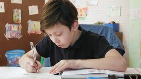 Χαριτωμένο μικρό παιδί που κάνει τις ασκήσεις από το βιβλίο σπουδαστών στο δωμάτιό του απόθεμα βίντεο