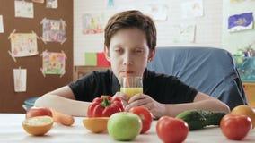 Χαριτωμένο μικρό παιδί που πίνει το χυμό από πορτοκάλι με ένα άχυρο σε έναν πίνακα με τα υγιή φρούτα και λαχανικά φιλμ μικρού μήκους