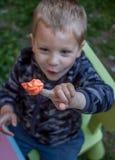 Χαριτωμένο μικρό παιδί που παρουσιάζει φωτεινό κομμάτι του plasticine στοκ εικόνες