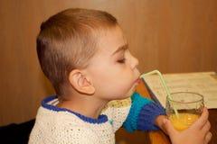 Χαριτωμένο μικρό παιδί που ρουφά γουλιά γουλιά το χυμό από πορτοκάλι Στοκ εικόνα με δικαίωμα ελεύθερης χρήσης