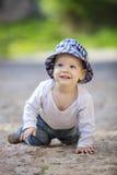 Χαριτωμένο μικρό παιδί που σέρνεται στρωμένο στο πέτρα πεζοδρόμιο Στοκ Φωτογραφίες