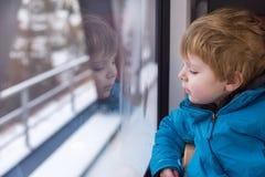Χαριτωμένο μικρό παιδί που φαίνεται έξω παράθυρο τραίνων Στοκ Εικόνες