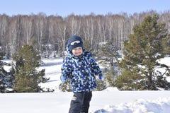 Χαριτωμένο μικρό παιδί που φορά τα θερμά ενδύματα που παίζουν στο χειμερινό δάσος επάνω στοκ εικόνες