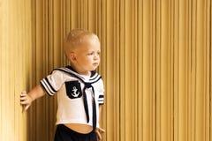 Χαριτωμένο μικρό παιδί σε ένα κοστούμι ναυτικών ` s που στέκεται ενάντια στον ξύλινο τοίχο διάστημα αντιγράφων Στοκ φωτογραφίες με δικαίωμα ελεύθερης χρήσης