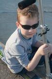 Χαριτωμένο μικρό παιδί στα γυαλιά ηλίου και ένα μηχανικό δίκυκλο έξω από την πόλη Στοκ εικόνα με δικαίωμα ελεύθερης χρήσης