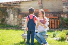 Χαριτωμένο μικρό παιδί, δόσιμο παρόν στο mom του για την ημέρα μητέρων στο θόριο στοκ εικόνα με δικαίωμα ελεύθερης χρήσης