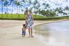 Χαριτωμένο μικτό μικρό παιδί φυλών που περπατά κατά μήκος της παραλίας με τη μητέρα του σε τροπικές διακοπές νησιών στοκ φωτογραφία