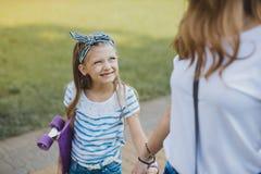 Χαριτωμένο μπλε-eyed κορίτσι που εξετάζει τη μητέρα της περπατώντας από κοινού στοκ εικόνα με δικαίωμα ελεύθερης χρήσης