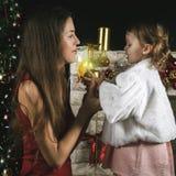 Χαριτωμένο μωρό και mum διακόσμηση ενός χριστουγεννιάτικου δέντρου κόκκινο σφαιρών Στοκ εικόνες με δικαίωμα ελεύθερης χρήσης