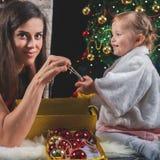 Χαριτωμένο μωρό και mum διακόσμηση ενός χριστουγεννιάτικου δέντρου κόκκινο σφαιρών Στοκ Φωτογραφία