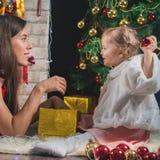 Χαριτωμένο μωρό και mum διακόσμηση ενός χριστουγεννιάτικου δέντρου κόκκινο σφαιρών Στοκ Εικόνες