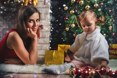 Χαριτωμένο μωρό και mum διακόσμηση ενός χριστουγεννιάτικου δέντρου κόκκινο σφαιρών Στοκ φωτογραφία με δικαίωμα ελεύθερης χρήσης