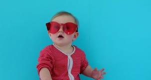 Χαριτωμένο μωρό με το παιδί στα κόκκινα γυαλιά ηλίου φιλμ μικρού μήκους