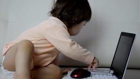 Χαριτωμένο μωρό με το φορητό προσωπικό υπολογιστή στο άσπρο γενικό υπόβαθρο φιλμ μικρού μήκους