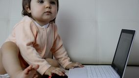 Χαριτωμένο μωρό με το φορητό προσωπικό υπολογιστή στο άσπρο γενικό υπόβαθρο απόθεμα βίντεο