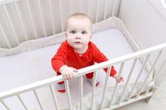 Χαριτωμένο μωρό 6 μηνών που στέκεται στο άσπρο κρεβάτι Στοκ εικόνες με δικαίωμα ελεύθερης χρήσης