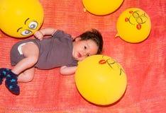Χαριτωμένο μωρό μικρών παιδιών που στηρίζεται στο έδαφος με τα κίτρινα μπαλόνια Στοκ φωτογραφία με δικαίωμα ελεύθερης χρήσης