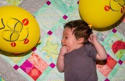 Χαριτωμένο μωρό μικρών παιδιών που στηρίζεται στο έδαφος με τα κίτρινα μπαλόνια Στοκ Εικόνες