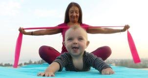 Χαριτωμένο μωρό που βρίσκεται κοντά στη γυναίκα που κάνει τη γιόγκα φιλμ μικρού μήκους