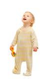Χαριτωμένο μωρό που στέκεται με το κουδούνισμα και που ανατρέχει στοκ εικόνα