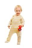 Χαριτωμένο μωρό που στέκεται με το κουδούνισμα στην άσπρη ανασκόπηση στοκ φωτογραφία