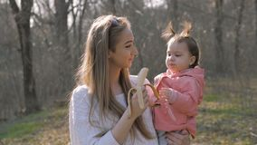 Χαριτωμένο μωρό που τρώει την μπανάνα στα όπλα της μητέρας απόθεμα βίντεο