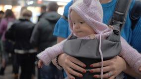 Χαριτωμένο μωρό σε έναν μεταφορέα μωρών απόθεμα βίντεο
