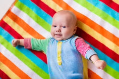 Χαριτωμένο μωρό σε ένα ζωηρόχρωμο κάλυμμα Στοκ φωτογραφία με δικαίωμα ελεύθερης χρήσης