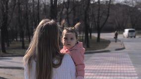 Χαριτωμένο μωρό στα όπλα της μητέρας της υπαίθρια απόθεμα βίντεο