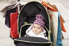 Χαριτωμένο μωρό στον περιπατητή που κρεμιέται με τις τσάντες αγορών Στοκ Φωτογραφίες
