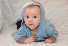 Χαριτωμένο μωρό στο πουλόβερ με την κουκούλα που βρίσκεται στο στομάχι του σε ένα μπλε κάλυμμα Στοκ φωτογραφίες με δικαίωμα ελεύθερης χρήσης