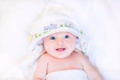 Χαριτωμένο μωρό υπό εξέταση - γίνοντη διαγώνια βελονιά με κουκούλα πετσέτα Στοκ εικόνα με δικαίωμα ελεύθερης χρήσης