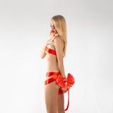 Χαριτωμένο νέο γυναίκα-δώρο με τις κόκκινες κορδέλλες στο σεξουαλικό λεπτό σώμα Στοκ εικόνα με δικαίωμα ελεύθερης χρήσης