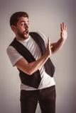 Χαριτωμένο νέο εκφοβισμένο άτομο με τη γενειάδα στο πουκάμισο και γιλέκο πέρα από το γκρίζο υπόβαθρο Στοκ φωτογραφία με δικαίωμα ελεύθερης χρήσης