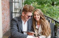 Χαριτωμένο νέο ερωτικό ζεύγος με μια ψηφιακή ταμπλέτα σε ένα θολωμένο υπόβαθρο νέα τεχνολογία έννοιας Στοκ Εικόνες