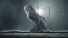 Χαριτωμένο νέο εύκαμπτο κορίτσι που αυξάνει το κεφάλι της με το αλεύρι στην τρίχα Νέα τοποθέτηση ballerina στο εγκαταλειμμένο κτή απόθεμα βίντεο